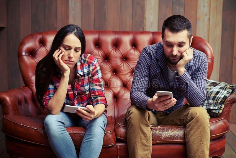 Coppia la seduta sullo strato che esamina i loro telefoni fotografie stock