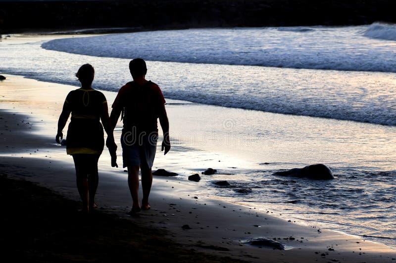 Coppia la siluetta che cammina alla spiaggia al tramonto fotografia stock libera da diritti