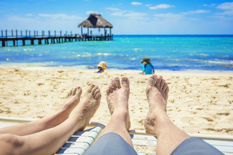 Coppia la sorveglianza dei loro bambini giocare sulla spiaggia sulla vacanza immagini stock