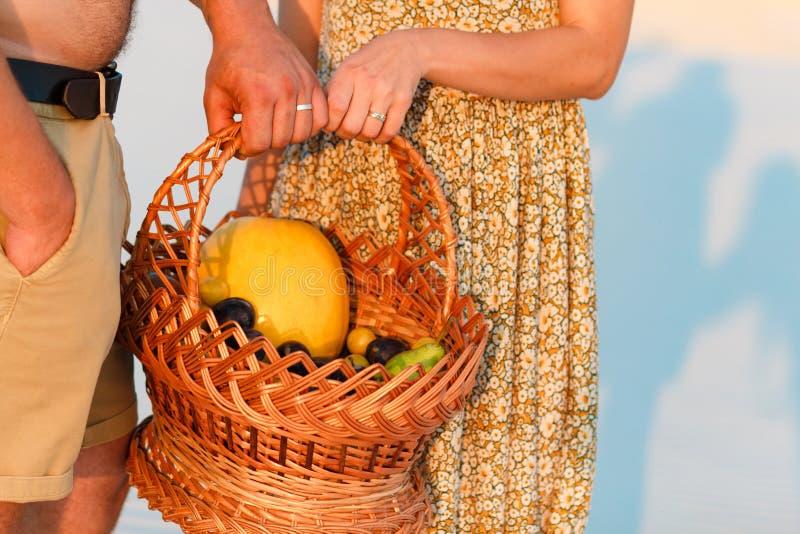 Coppia la tenuta del canestro di vimini con frutta, l'uomo e la donna aventi un picnic sulla spiaggia di sabbia bianca o nel dese fotografia stock libera da diritti