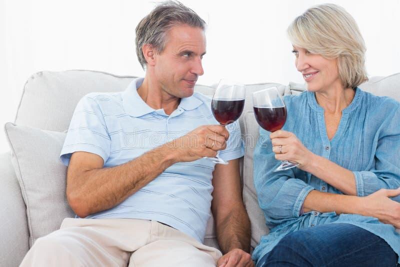 Coppia la tostatura con il vino rosso sul sofà immagini stock