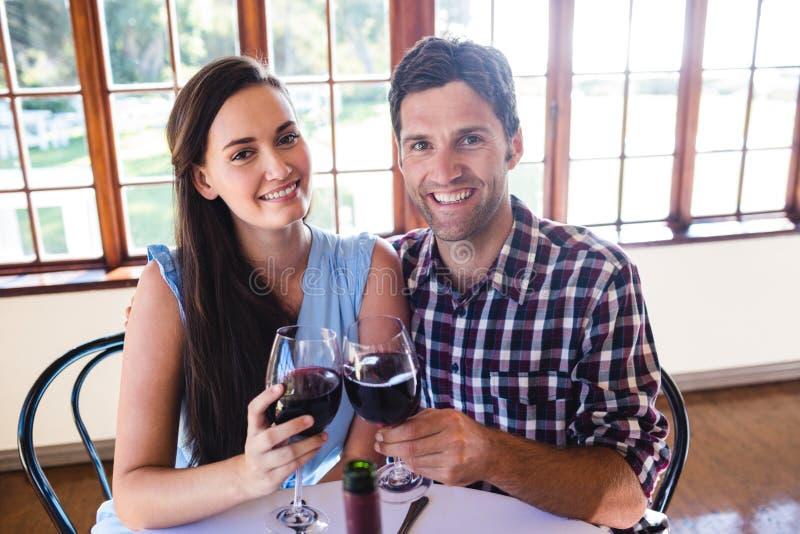 Coppia la tostatura del vetro del vino rosso in ristorante fotografia stock