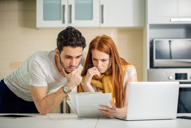 Coppia le finanze in carico, esaminanti i conti bancari facendo uso del computer portatile fotografia stock
