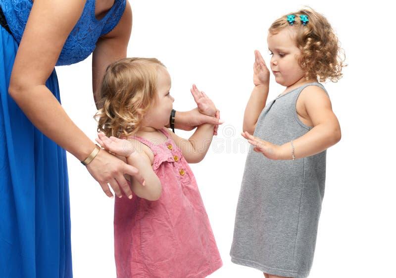 Coppia le giovani bambine con la madre che controlla il fondo bianco immagine stock libera da diritti