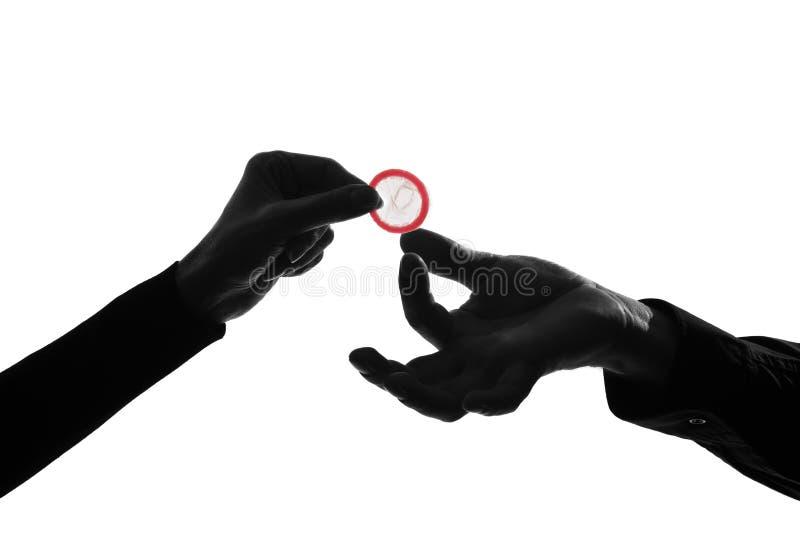 Coppia le mani della donna e dell'uomo che tengono dare a preservativo alto vicino fotografia stock libera da diritti