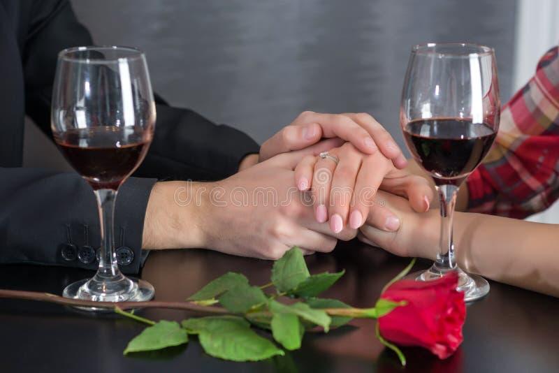Coppia le mani sulla tavola del ristorante con due vetri di vino rosso e delle rose immagine stock