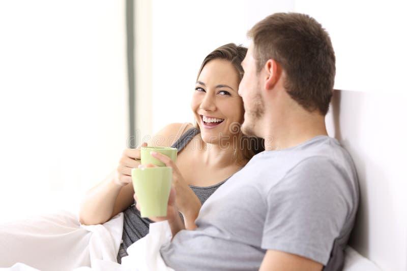 Coppia mangiare la prima colazione e la conversazione su un letto immagine stock libera da diritti