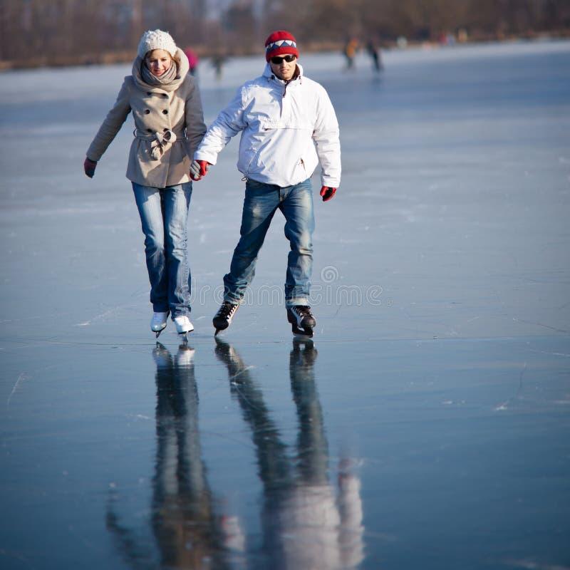 Coppia pattinare di ghiaccio su uno stagno fotografie stock
