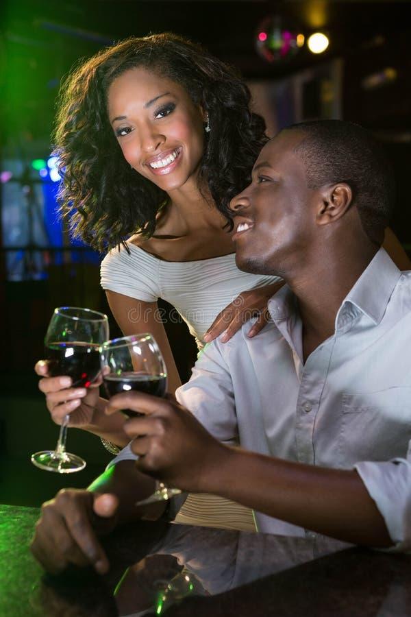 Coppia sorridere e la tostatura dei loro vetri di vino al contatore della barra fotografie stock