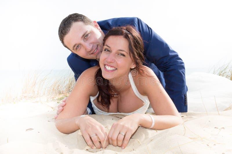 Coppia sposata allegra che si trova sulla spiaggia fotografia stock libera da diritti