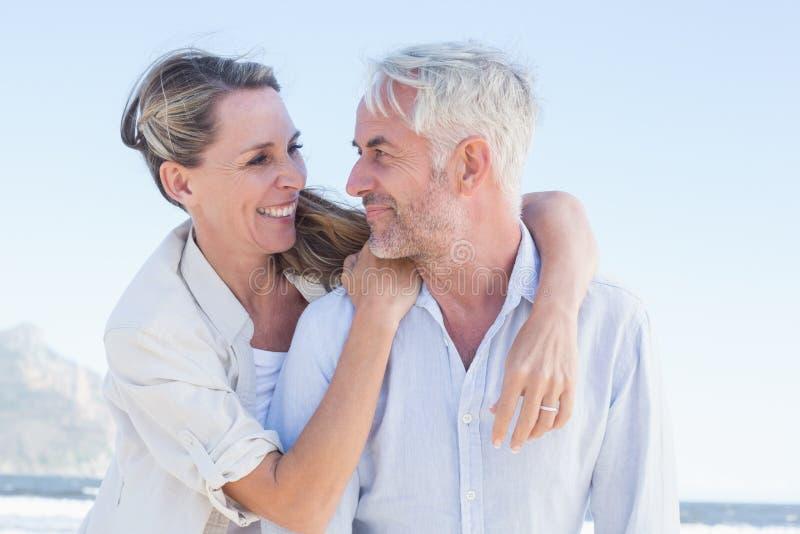 Coppia sposata attraente che abbraccia alla spiaggia immagine stock libera da diritti