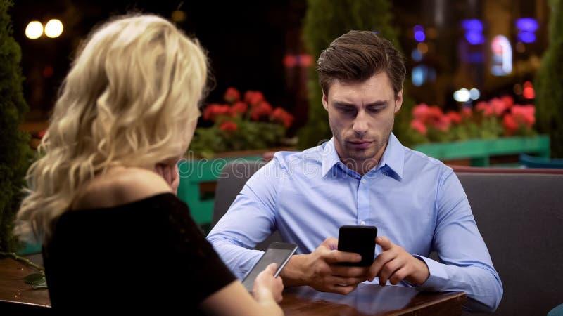 Coppia sposata che non presta attenzione che fa scorrere l'un l'altro le pagine sugli smartphones immagine stock