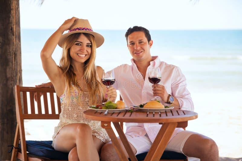 Coppie abbastanza giovani che mangiano alla spiaggia fotografia stock libera da diritti