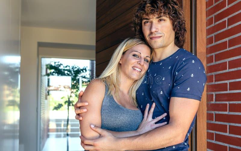 Coppie abbracciate all'entrata della loro casa fotografia stock