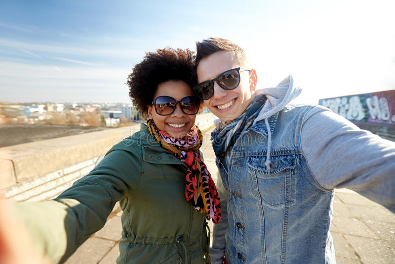 Coppie adolescenti felici che prendono selfie sulla via della città fotografia stock