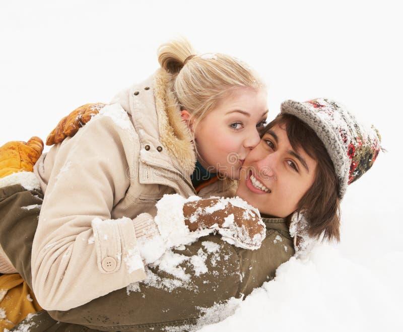 Coppie adolescenti romantiche che hanno divertimento in neve fotografie stock libere da diritti