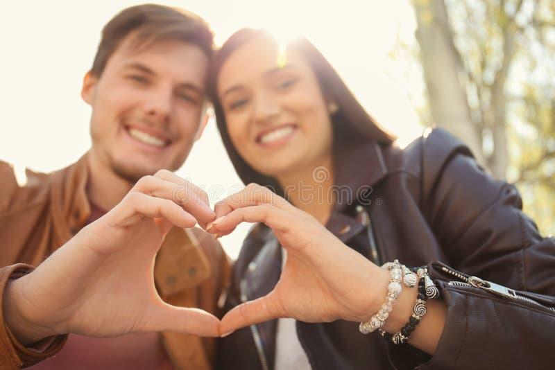 Coppie adorabili che si tengono per mano nella forma di cuore all'aperto immagine stock libera da diritti