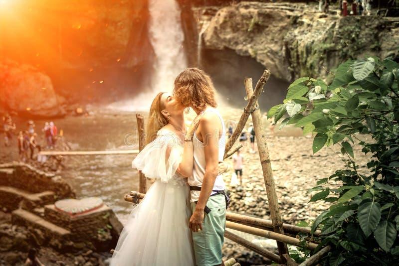 Coppie adorabili di nozze contro la cascata sul tramonto, isola tropicale di Bali fotografie stock