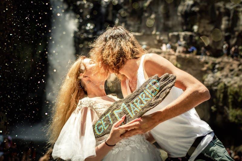 Coppie adorabili di nozze contro la cascata sul tramonto, isola tropicale di Bali fotografie stock libere da diritti