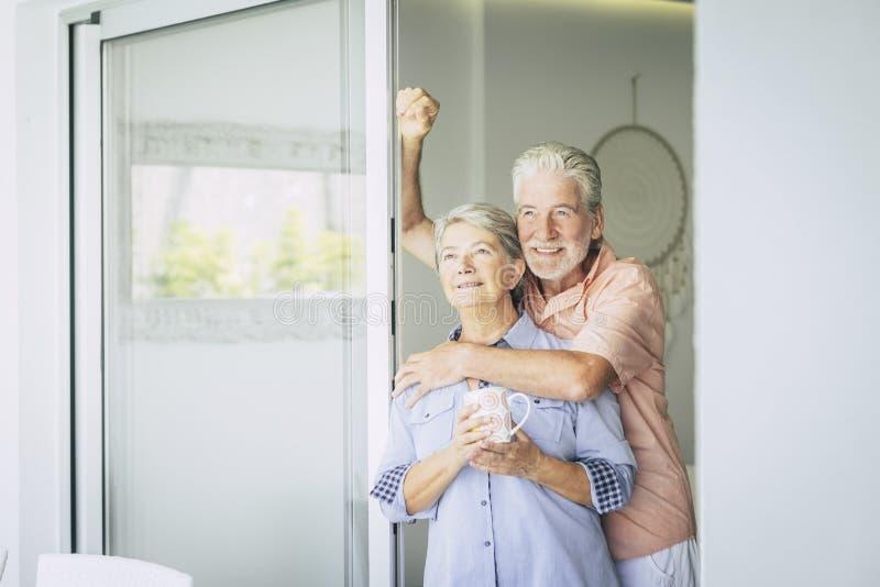 Coppie adulte allegre a casa che guardano fuori insieme alla gioia ed alla pace uomo felice e donna caucasici pensionati che godo immagini stock libere da diritti
