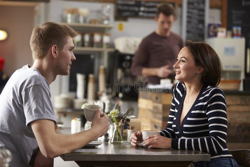 Coppie adulte che parlano ad una tavola in una caffetteria, vista laterale fotografie stock libere da diritti