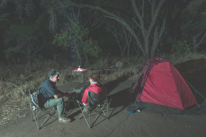 Coppie adulte che si rilassano nel campeggio di notte Avventura in parco nazionale, Sudafrica Fuoco bruciante e tenda del campo n immagine stock
