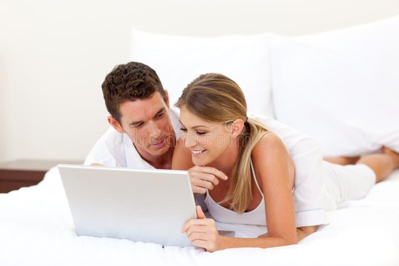 Coppie affettuose per mezzo di un computer portatile immagini stock libere da diritti