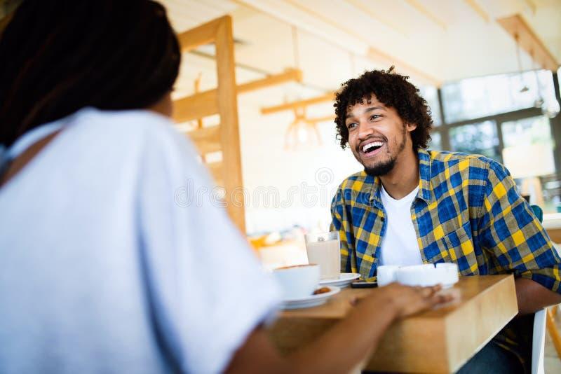 Coppie africane felici che datano in caffetteria e latte bevente immagini stock