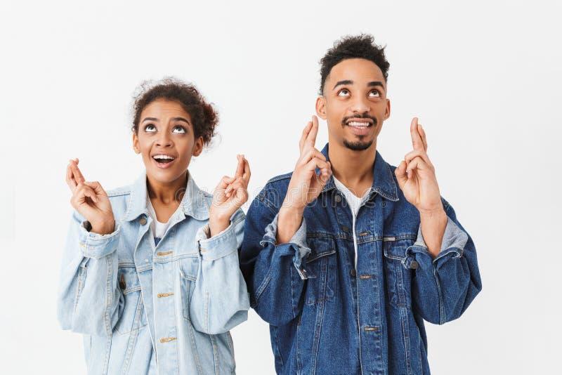 Coppie africane sorridenti in camice del denim che pregano insieme immagini stock libere da diritti