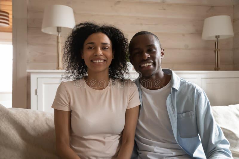 Coppie africane sorridenti che si siedono sullo strato che fa video chiamata immagine stock