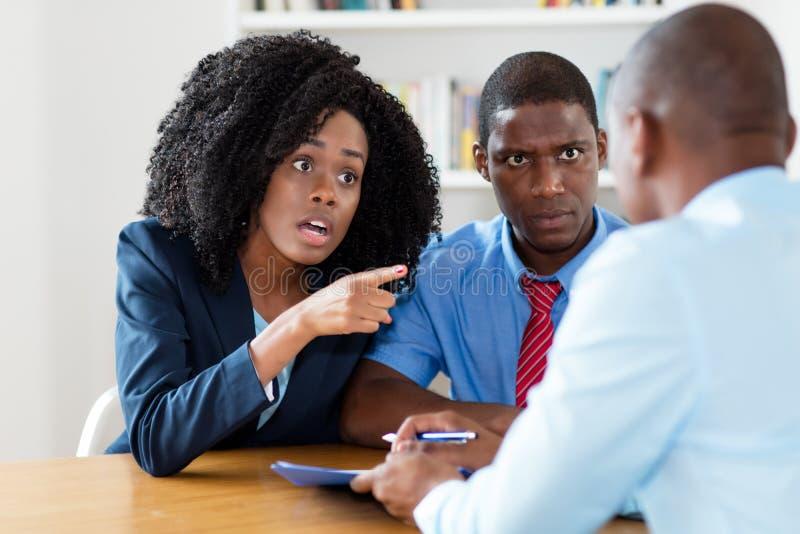 Coppie afroamericane arrabbiate che rifiutano offerta dell'agente immobiliare fotografia stock