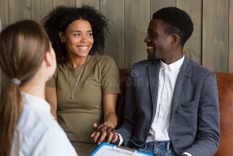 Coppie afroamericane felici riconciliate dopo riuscito psico immagine stock