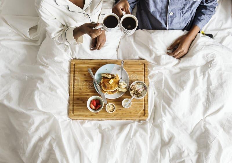 Coppie afroamericane a letto che mangiano una prima colazione a letto fotografia stock