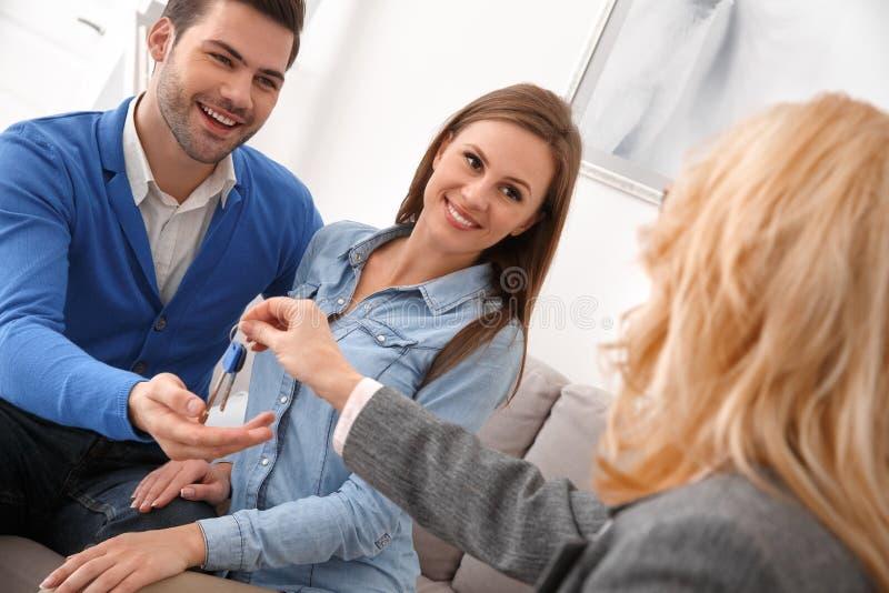 Coppie all'ufficio vendite del bene immobile con l'agente che fornisce le chiavi fotografia stock libera da diritti