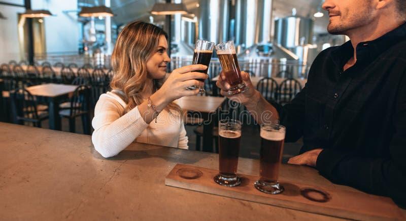 Coppie alla barra con differenti varietà di birre del mestiere fotografia stock