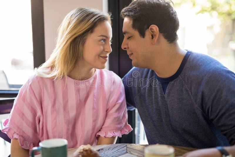 Coppie alla data che flirta in un caffè immagini stock