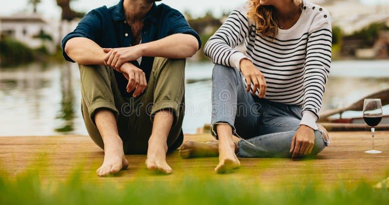 Coppie alla data che si siede vicino ad un lago con le bevande fotografia stock libera da diritti