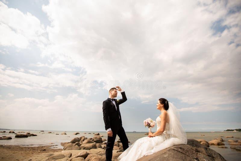 Coppie alla moda di nozze che stanno sulla riva di mare Le persone appena sposate stanno camminando dal mare immagini stock