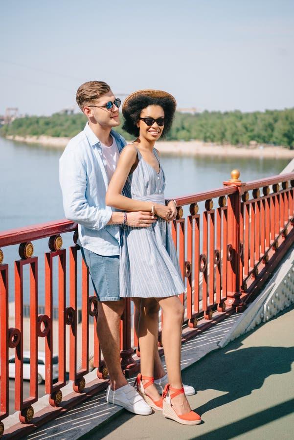 coppie alla moda multietniche in occhiali da sole che stanno sul ponte fotografia stock