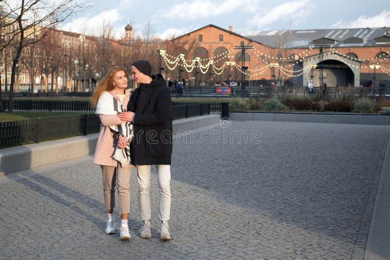 coppie alla moda nell'amore che cammina nel parco pubblico nella sera di festa fotografia stock libera da diritti