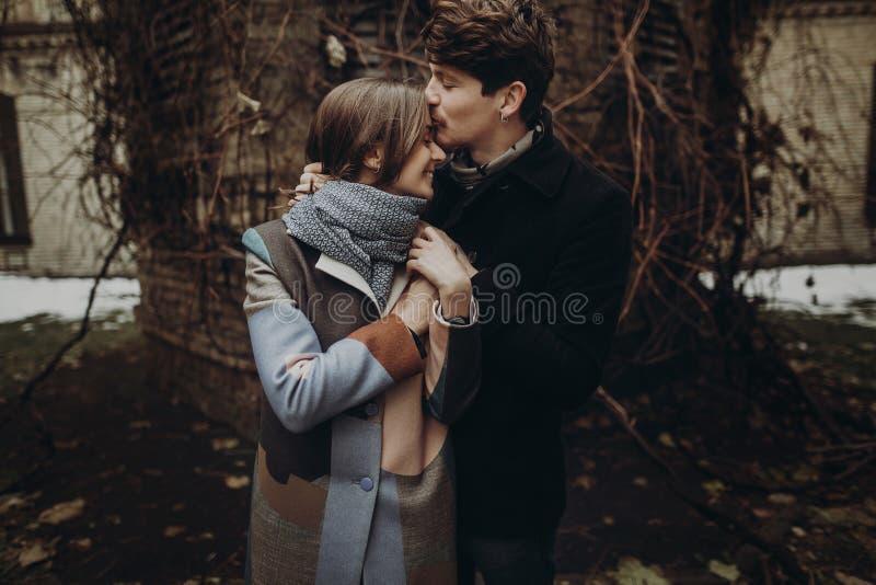 Coppie alla moda romantiche che abbracciano delicatamente nel parco di autunno uomo e w fotografia stock