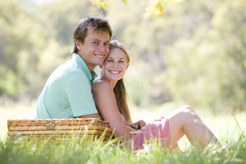 Coppie alla sosta che ha un picnic e sorridere fotografia stock