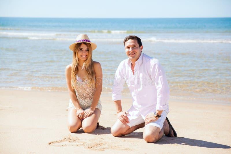 Coppie alla spiaggia che assorbe la sabbia fotografia stock