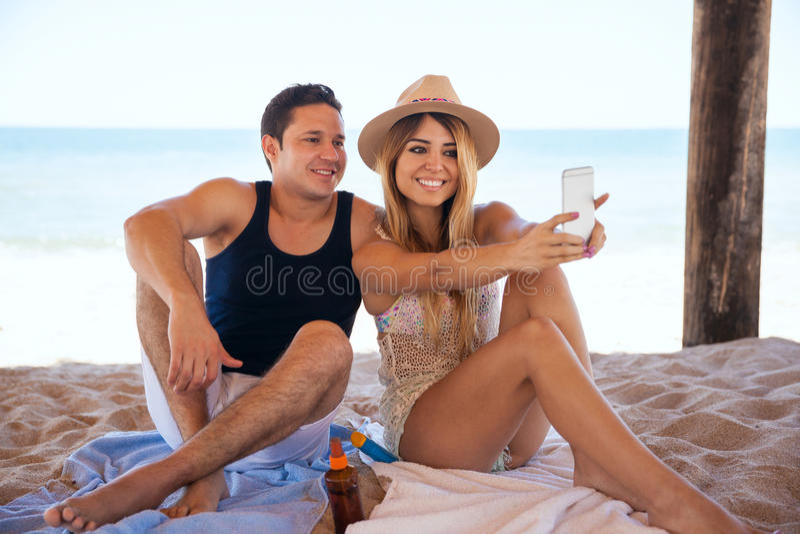 Coppie alla spiaggia che prende un selfie fotografia stock