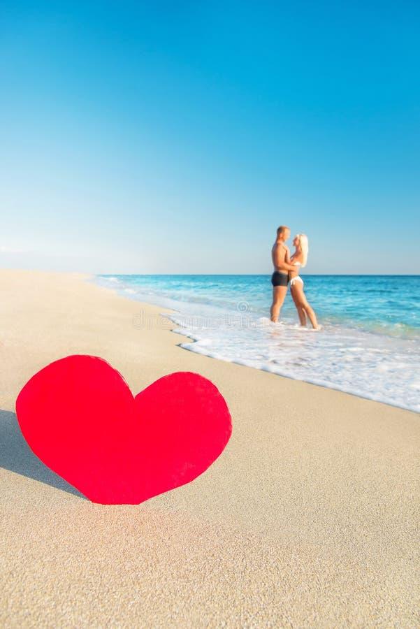 Coppie alla spiaggia del mare ed al grande cuore rosso fotografia stock