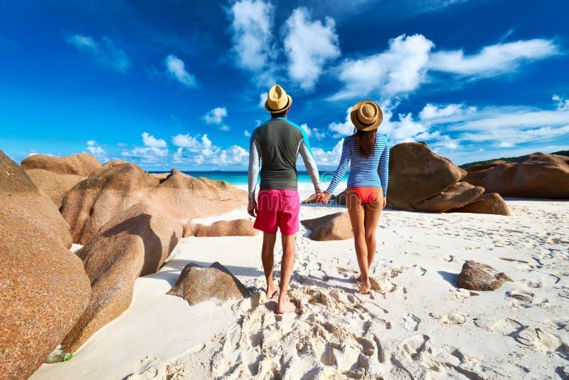 Coppie alla spiaggia tropicale che indossa guardia impetuosa fotografia stock