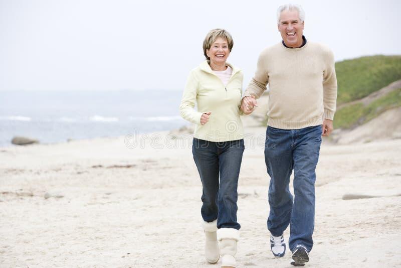 Coppie alle mani ed a sorridere della holding della spiaggia fotografia stock libera da diritti