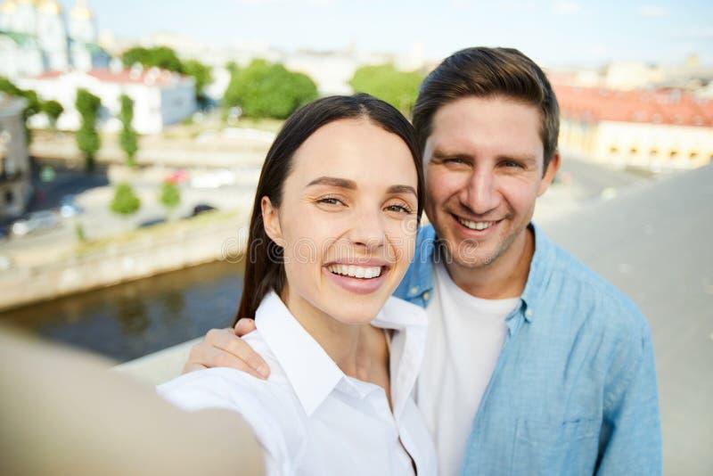 Coppie allegre che abbracciano mentre prendendo selfie immagini stock