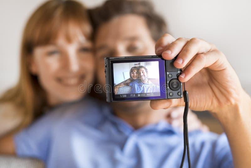 Coppie allegre che prendono un selfie con una macchina fotografica Backgr domestico bianco fotografia stock libera da diritti