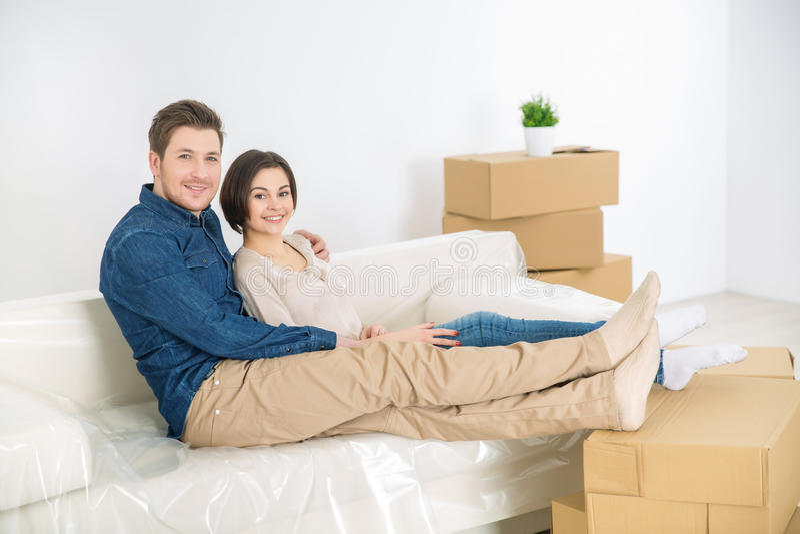 Coppie allegre che riposano sul sofà fotografia stock